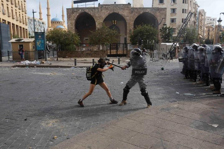 A policeman strikes a protester during anti-government demonstrations on August 8, 2020 in Beirut, Lebanon.