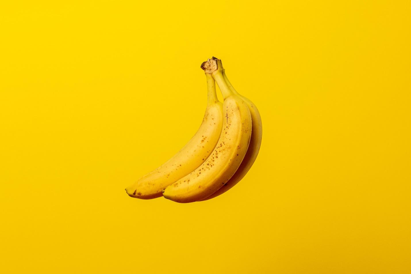 Ripe bananas against a yellow background