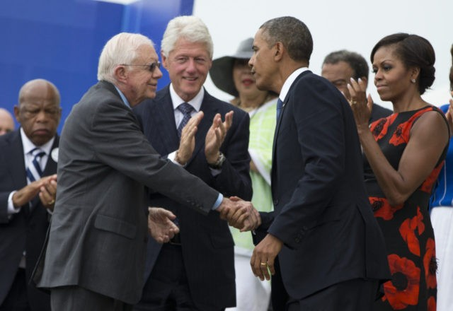 "President Barack Obama shakes hands with former President Jimmy Carter, left, during a ceremony commemorating the 50th anniversary of the March on Washington, Wednesday, Aug. 28,2013, at the Lincoln Memorial in Washington. The president was set to lead civil rights pioneers Wednesday in a ceremony for the 50th anniversary of the March on Washington, where Dr. Martin Luther King's ""I Have a Dream"" speech roused the 250,000 people who rallied there decades ago for racial equality. From left, Carter, former President Bill Clinton, Obama, and first lady Michelle Obama. (AP Photo/Evan Vucci)"