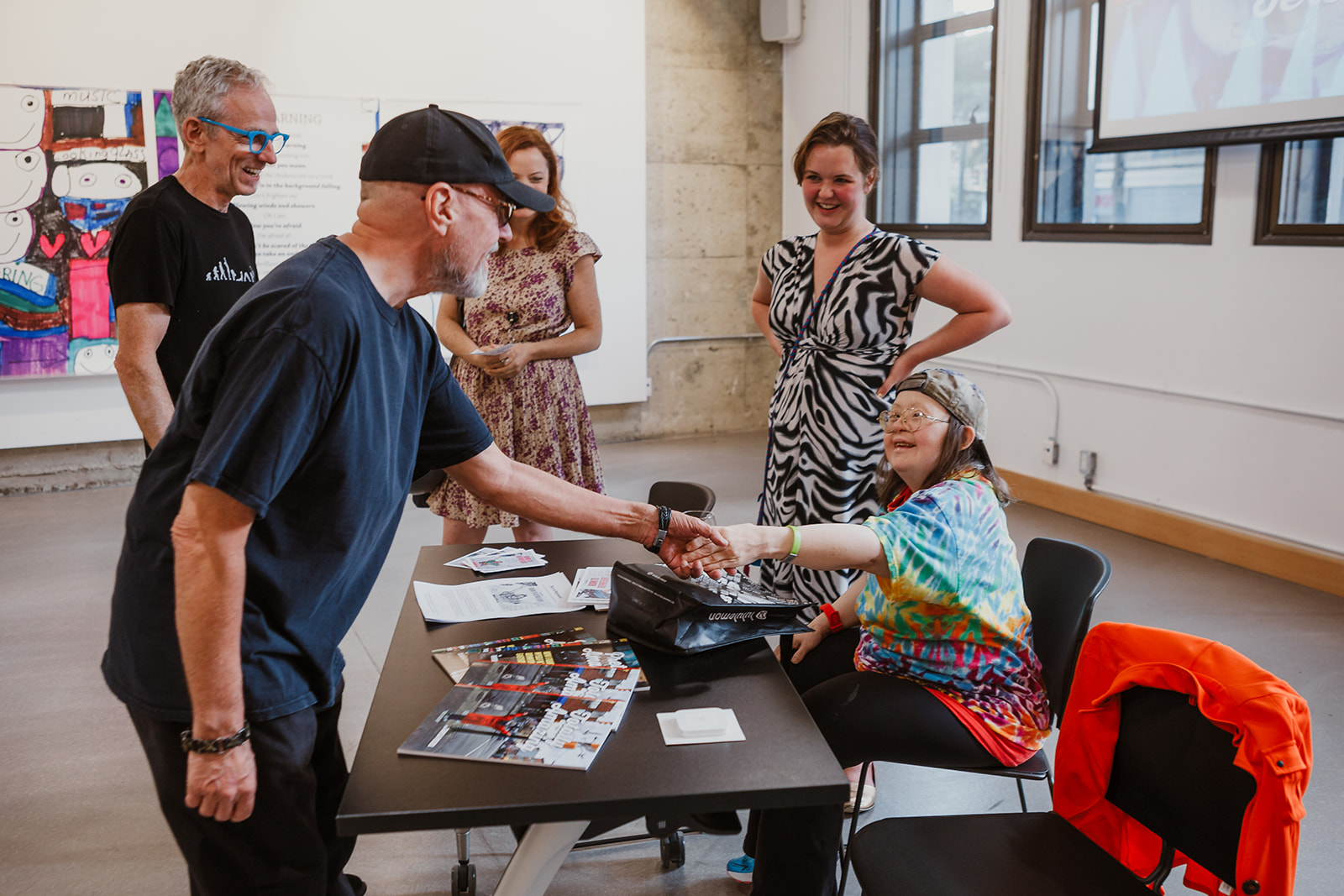 DTES artist Edzy shakes Teresa's hand as she sits by her book table on July 22, 2019. Photo: This Is It Studios.