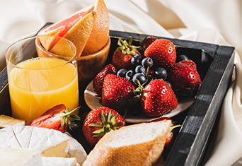 A tray filled with a slice of baguette, a plate of strawberries and blueberries, a bowl of pink grapefruit, a plate of cheese and a glass of orange juice