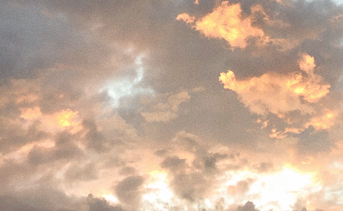 A group of clouds in the sky, it is sunset. The sun sets the clouds glow from behind. One an almost make out the shape of a deer in a break between two clouds.