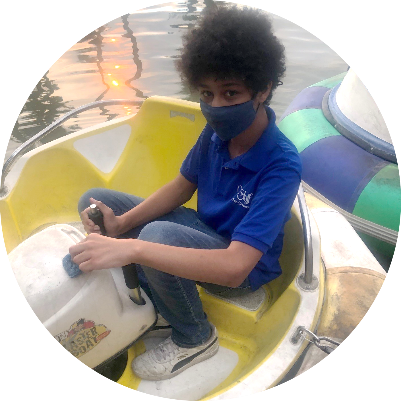 Adam - A Black young man with medium length curly hair sitting in a bumper boat.