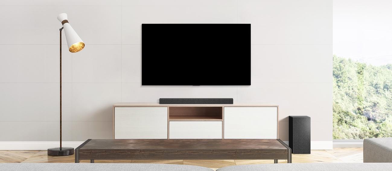 V, loa soundbar và loa siêu trầm được đặt trong phòng khách đơn giản.