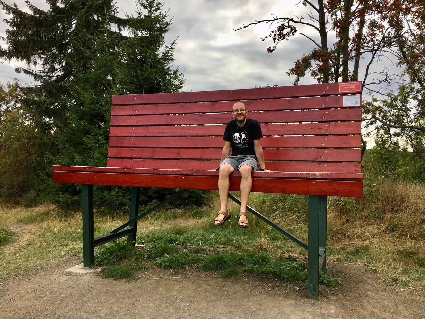 A person sitting on a red bench  Description automatically generated