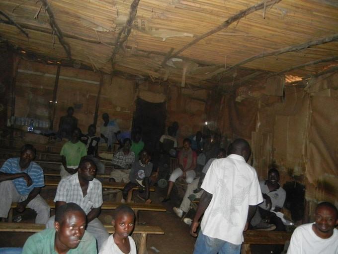 Una carpa en Wakaliga con gente sentada en bancadas esperando para ver una película.