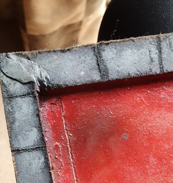 A joined corner of the painted board, showing a gap filled with modelling putty, and a groove in the red-painted base