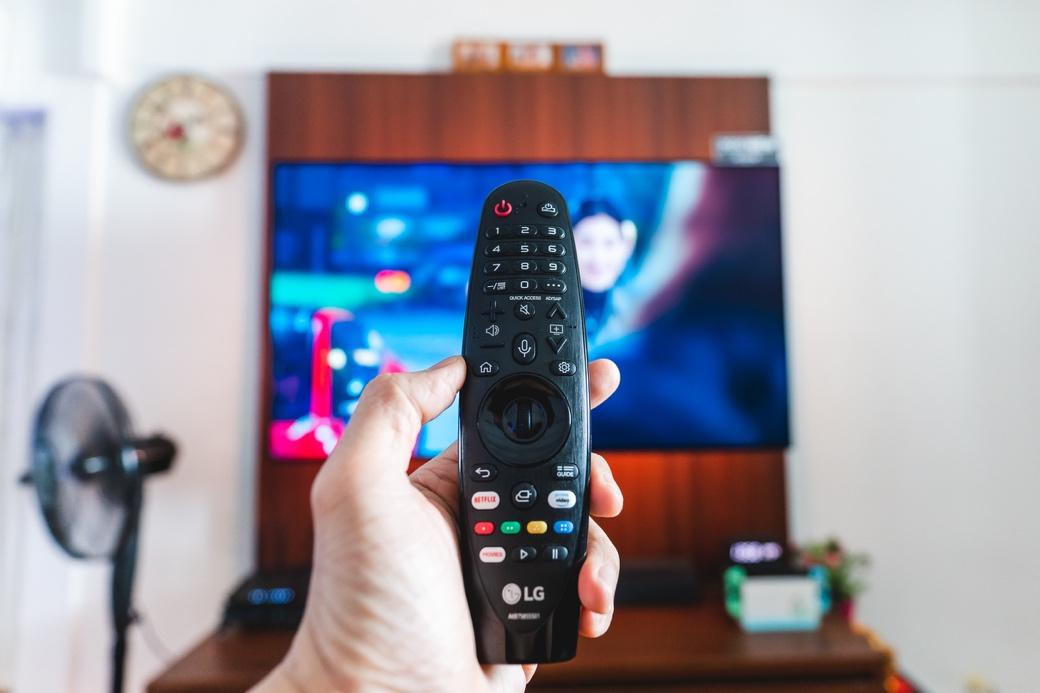 A hand holding a remote control  Description automatically generated