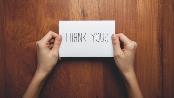 phot of hands holding a thank you note.