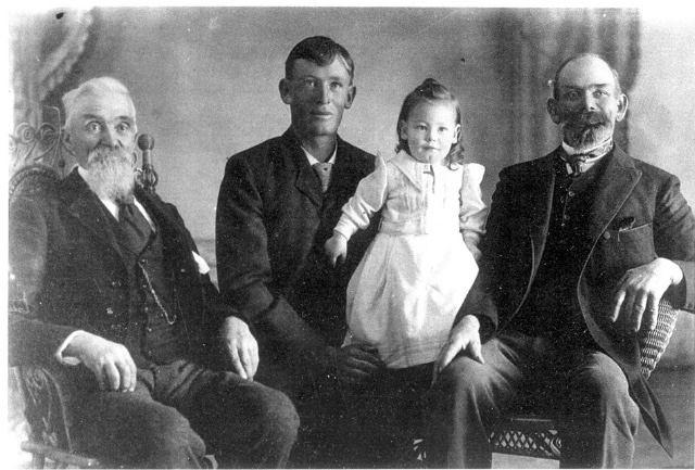 Four generations of Pyper men. John Pyper (age 76/77) on far right with gray head and facial hair. His grandson, John Barton Pyper (age 24/25) sits next to him and is clean shaven. On John Barton's lap sits Harold Johnson Pyper (age about 1 year) in a white ankle length baby dress (which contrasts with the dark black suits of the other men) and shoulder length curled hair. On the far right is, John Barton's father, James Munro Gardner Pyper (age 49/50). He has dark facial hair that looks like it is starting to go gray. He also has a severely receding hairline on top. The picture is a portrait style photo that looks as if it was taken inside of a photo studio.