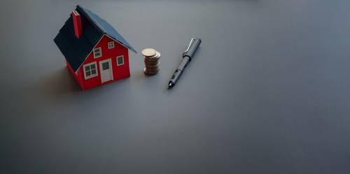 Mini house with stack of coins and pen on grey surface
