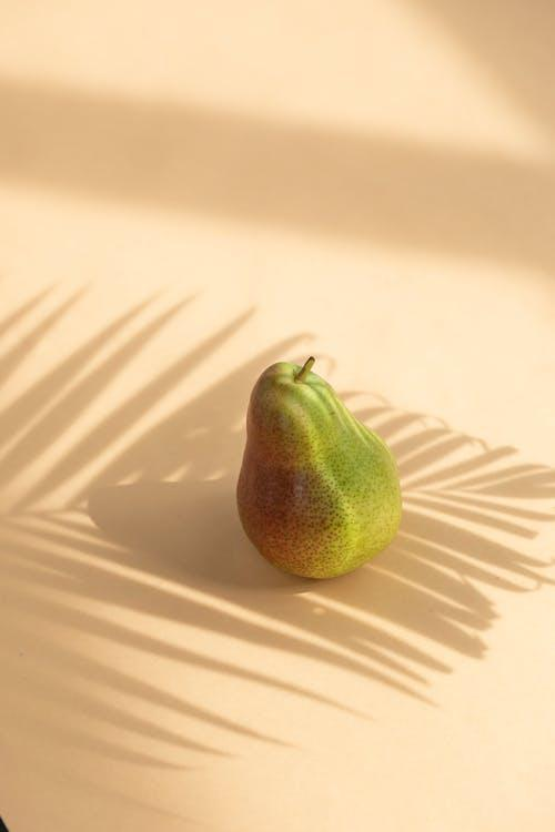 Ripe green and red fruit pear on white surface under palm branch