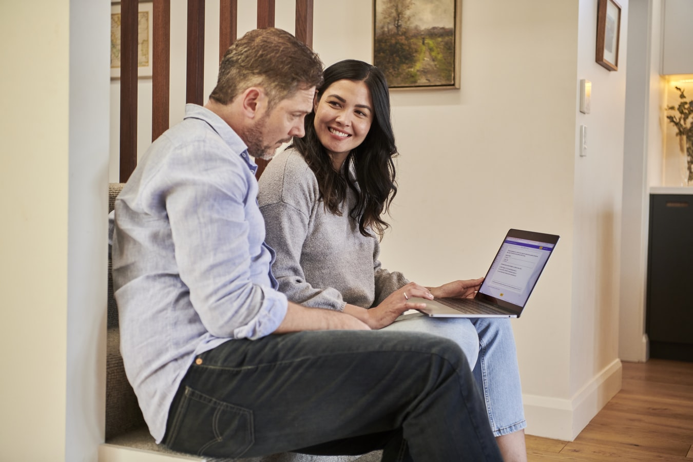 Couple sitting together with laptop