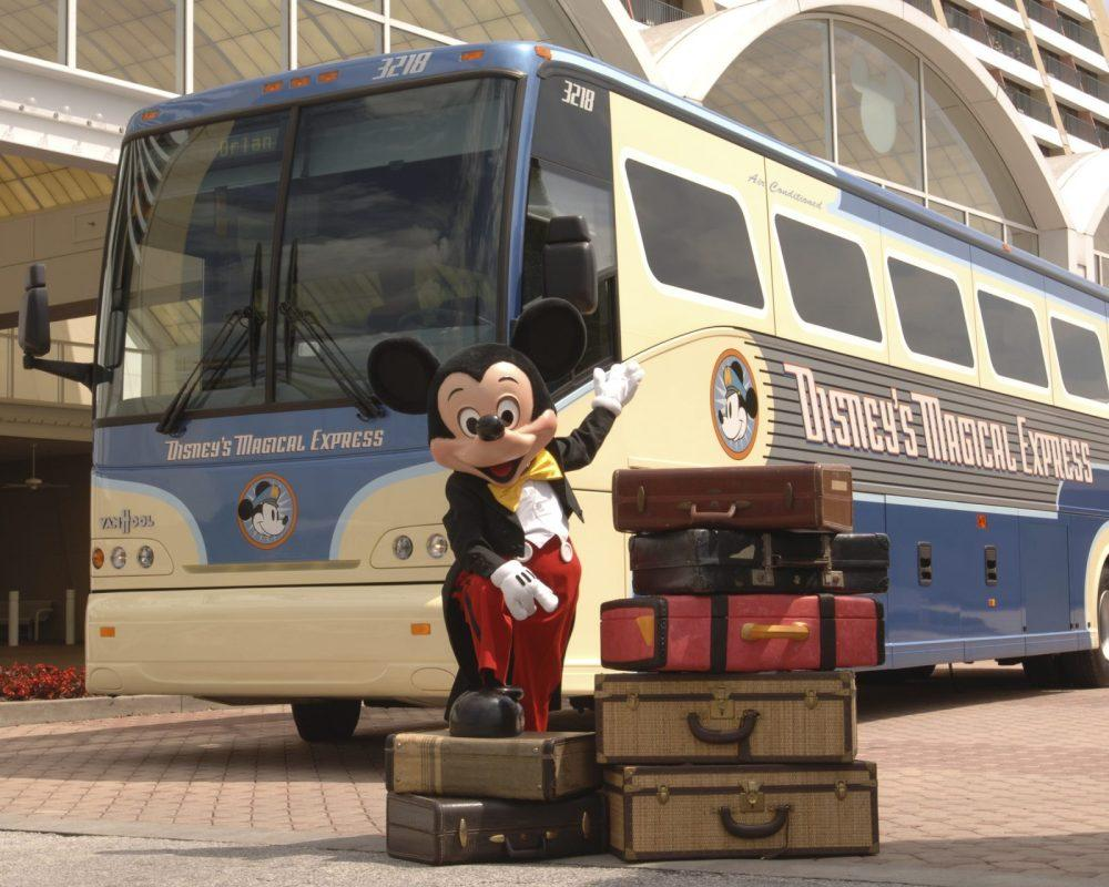 Disney Magical Express bus and Mickey Mouse standing in front with luggage pointing to the bags and bus.