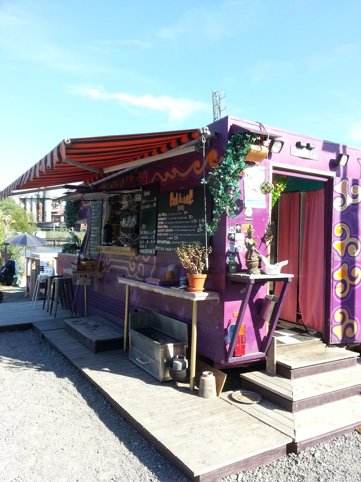 The image shows the café - a purple trailer with two steps up to the window for ordering. Menus are displayed at the front.