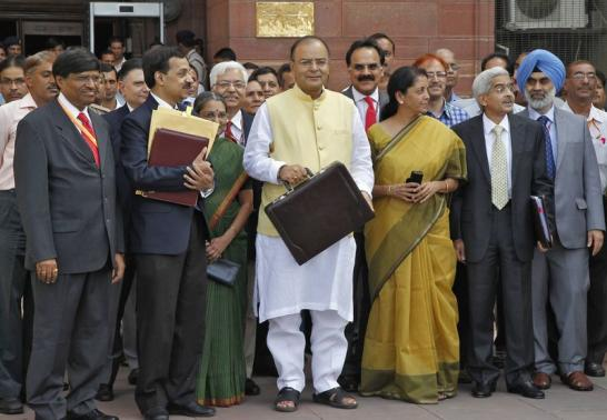 Finance Minister Arun Jaitley (C) poses as he leaves his office to present the federal budget for the 2014-15 fiscal year, in New Delhi July 10, 2014. REUTERS-Stringer