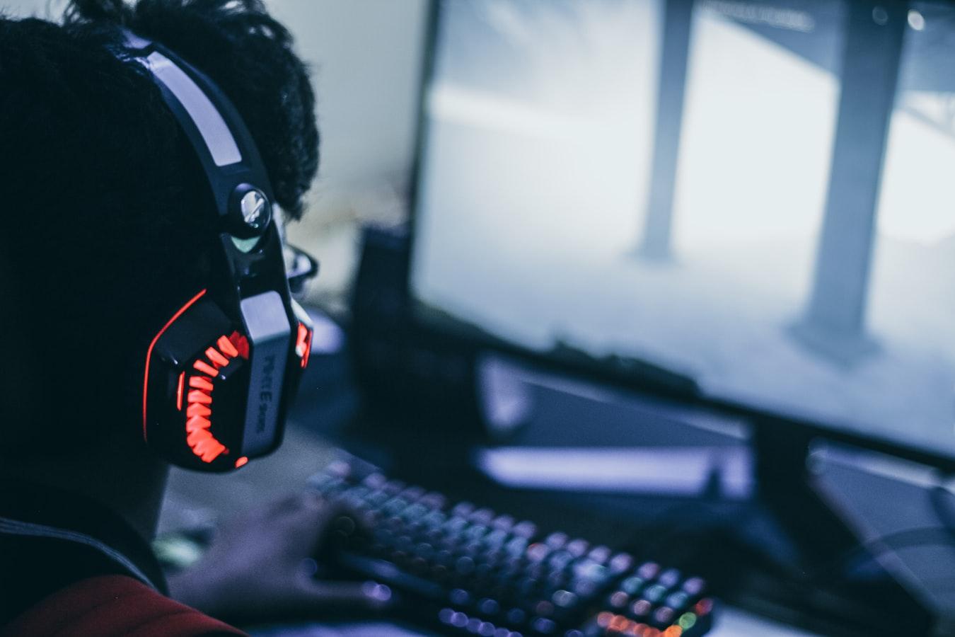 Um menino jogando no computador.