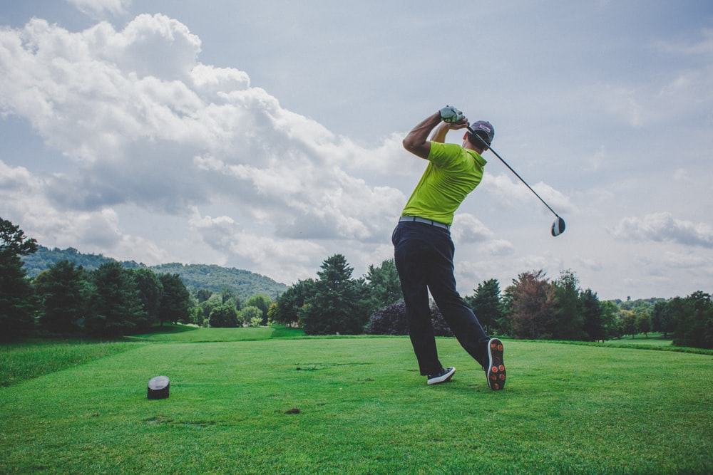 photo of man swinging golf driver