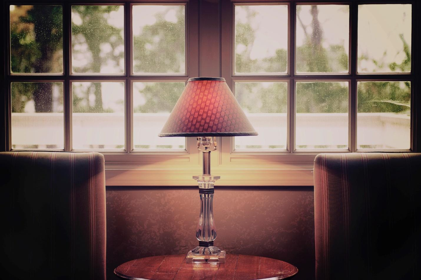 A table lamp in front of a window.