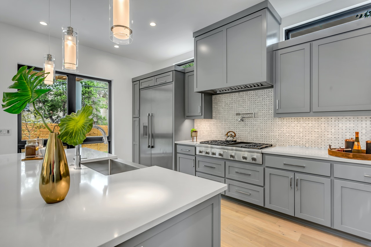 Grey slab cabinets create a chic industrial look for your kitchen; smooth grey cabinets with a grey island placed on wooden flooring.