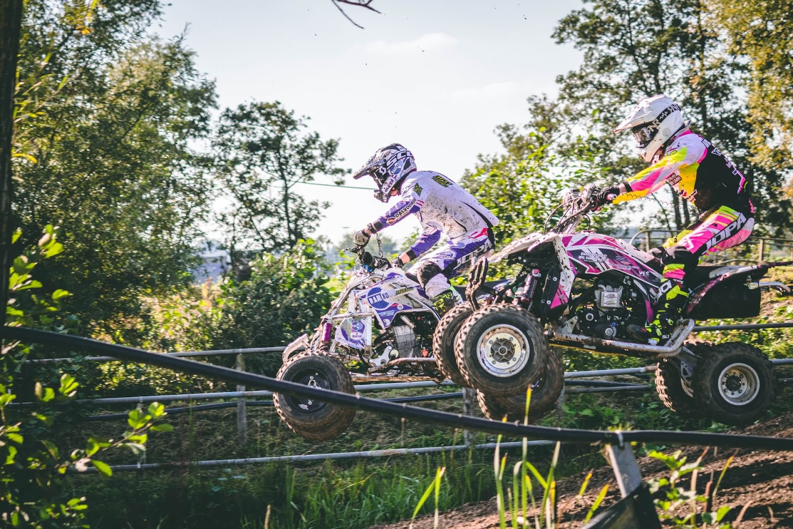 two people on a quad bike zooming through the muddy terrain