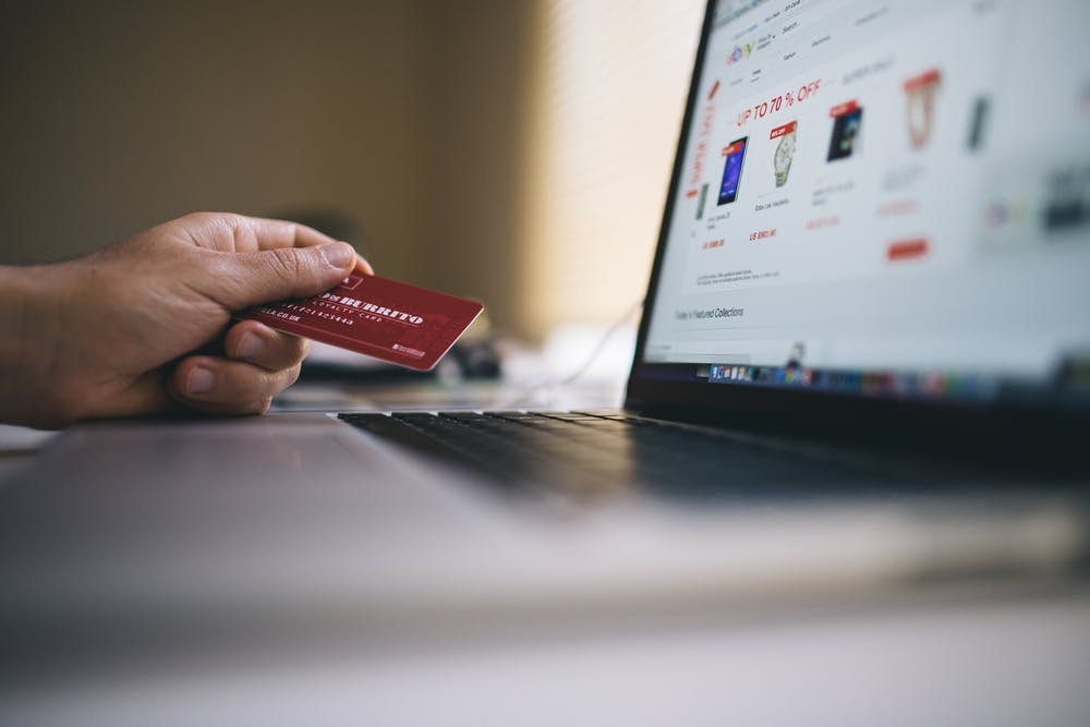 man's hand holding a credit card in front of laptop paying on ecommerce site