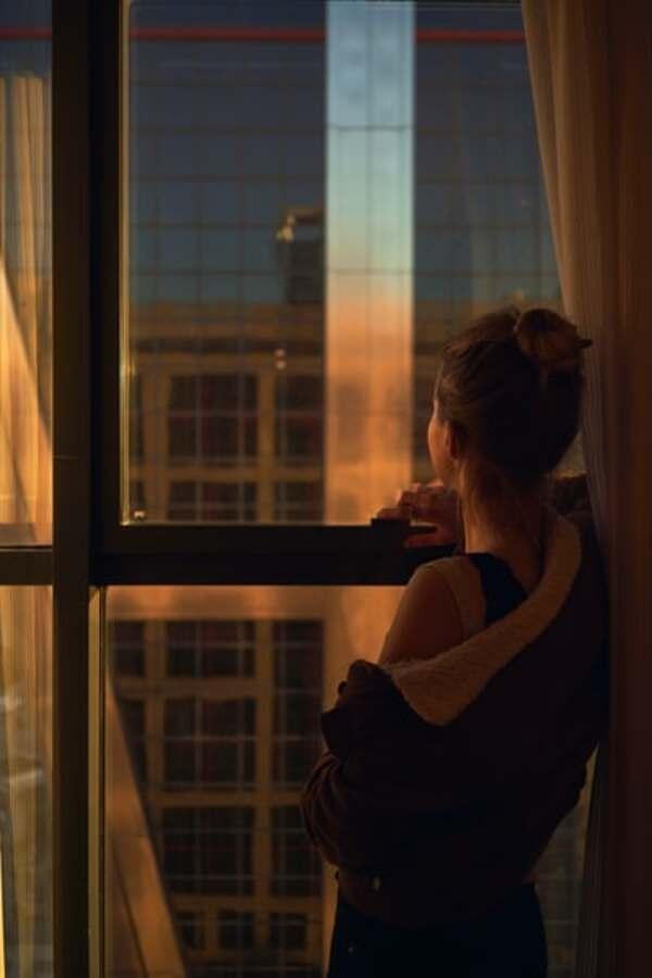 Foto de uma menina olhando pela janela