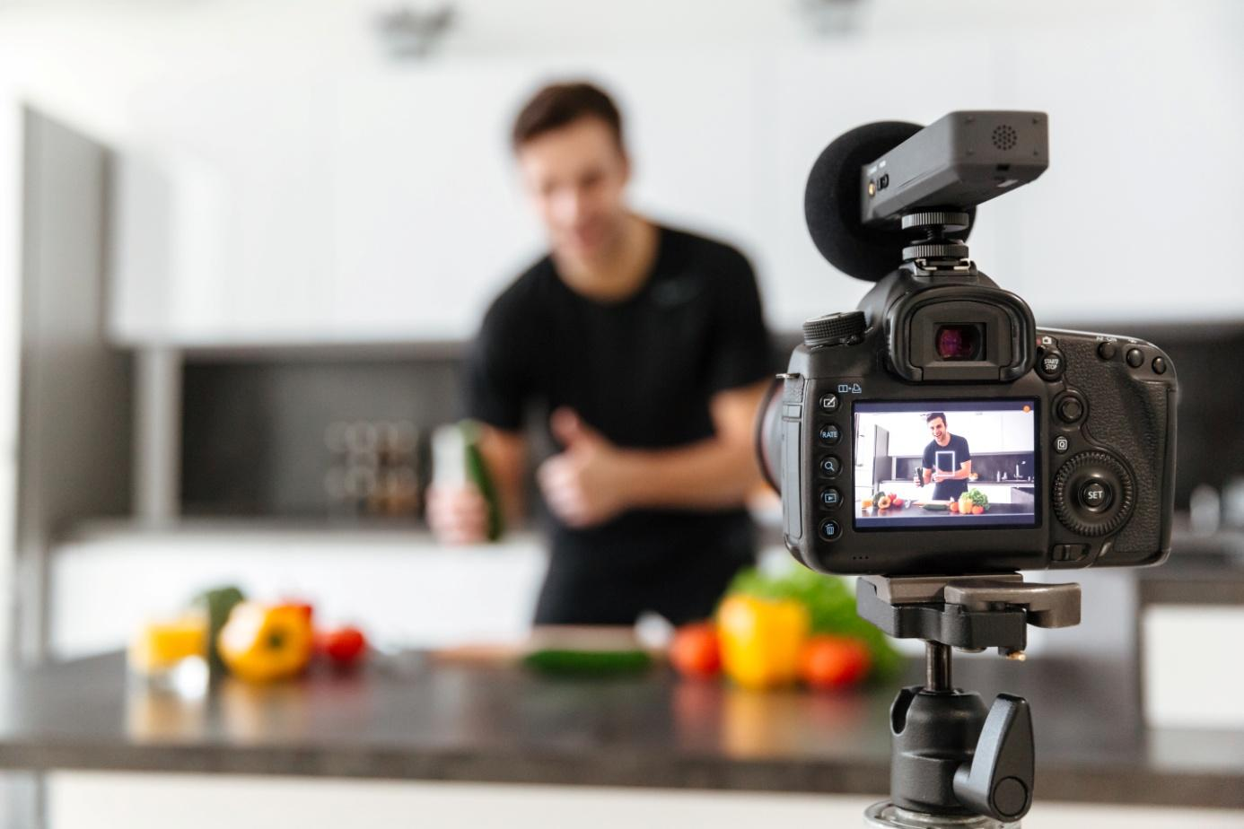 close-up-video-camera-filming-young-smiling-male-blogger.jpg