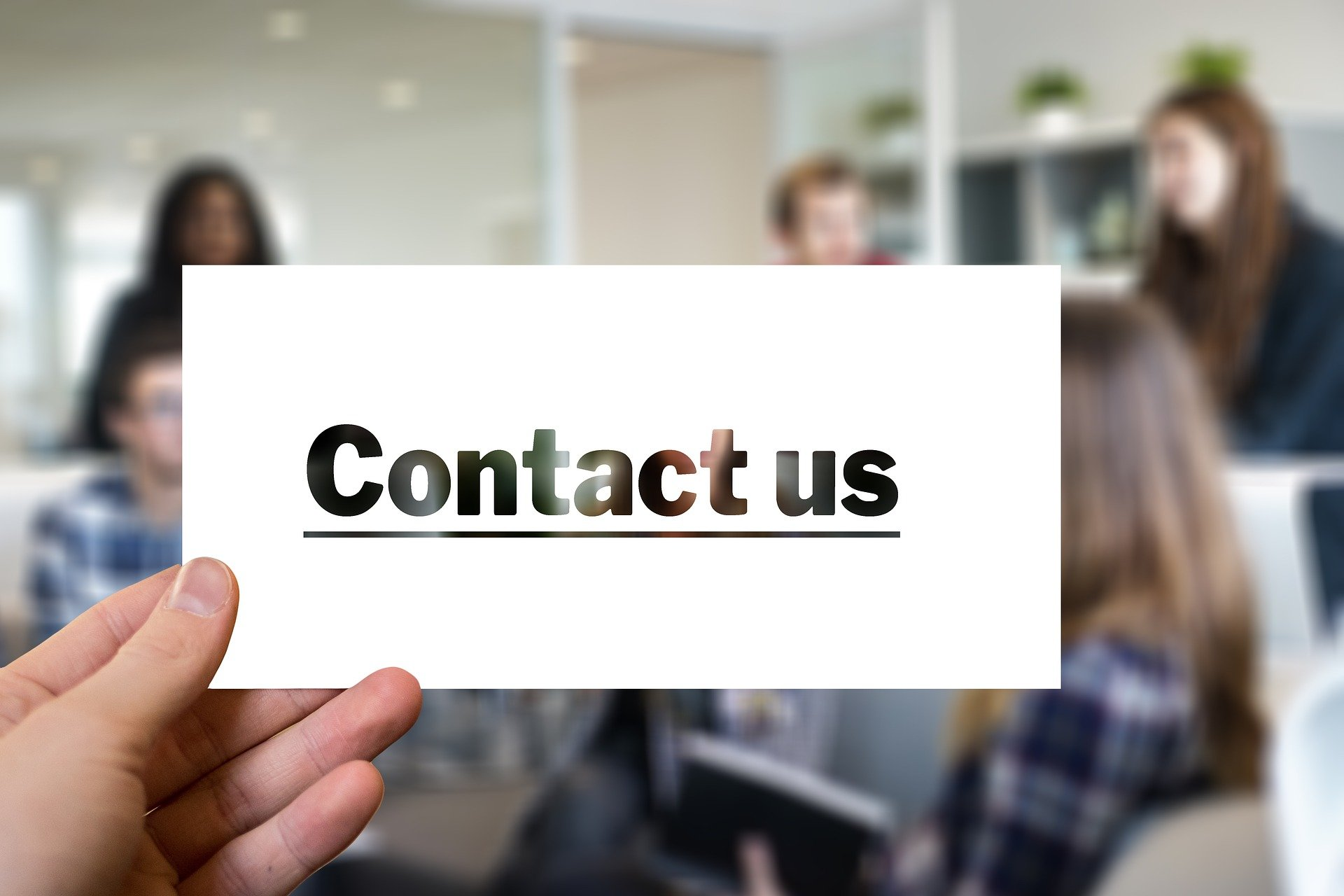 a hand holding up a piece of card saying 'contact us'.
