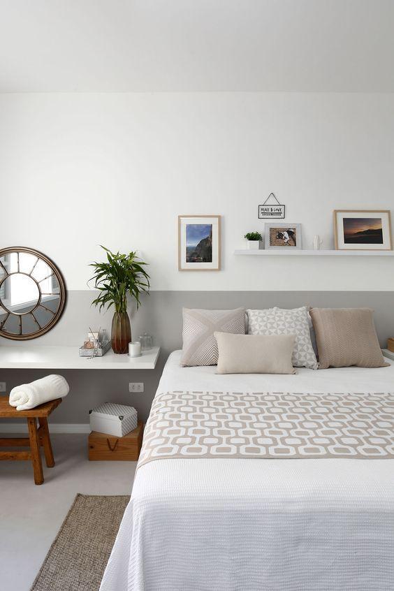 Quarto com cama de casal e parede com técnica de pintura meia parede branca e cinza, quadros decorativos e piso porcelanato branco.