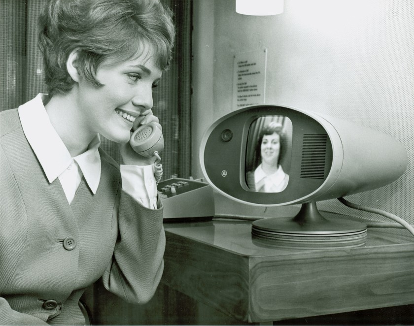 An image of a woman using the AT&T Picturephone, which looks like a landline connected to a small, rounded midcentury television.