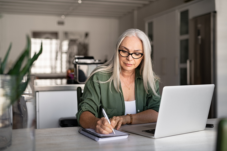 an older woman sitting in front of a laptop taking notes