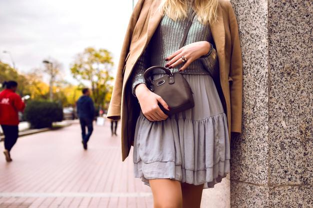 Close up fashion details, woman stay in the street, spring time, silk dress and cashmere coat, silver sweater and cross body bag, feminine elegant glamour outfit Free Photo