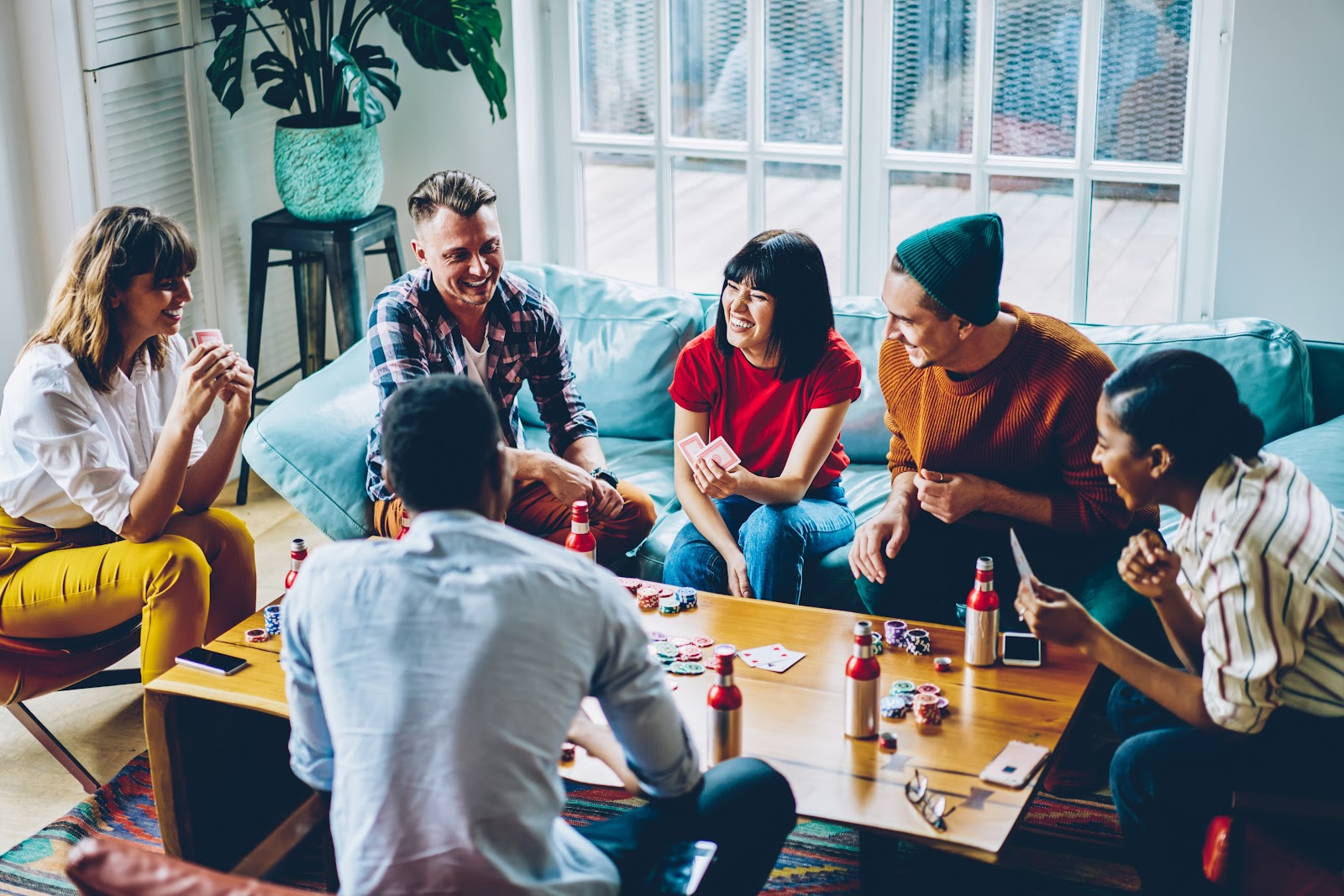 Six friends play poker around a coffee table.