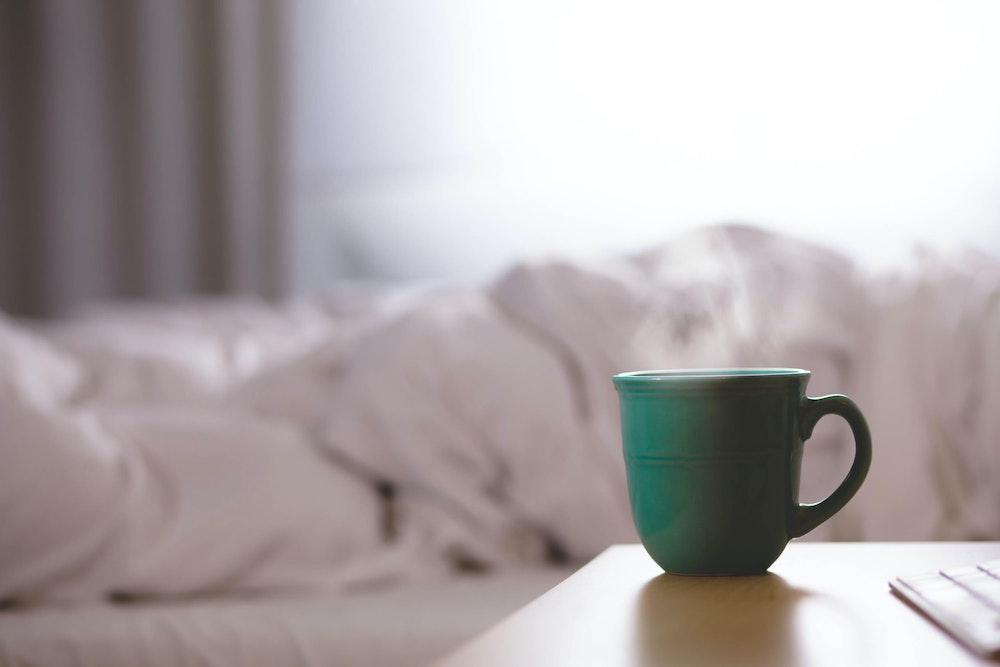 A mug on a bedside table with a bed in background