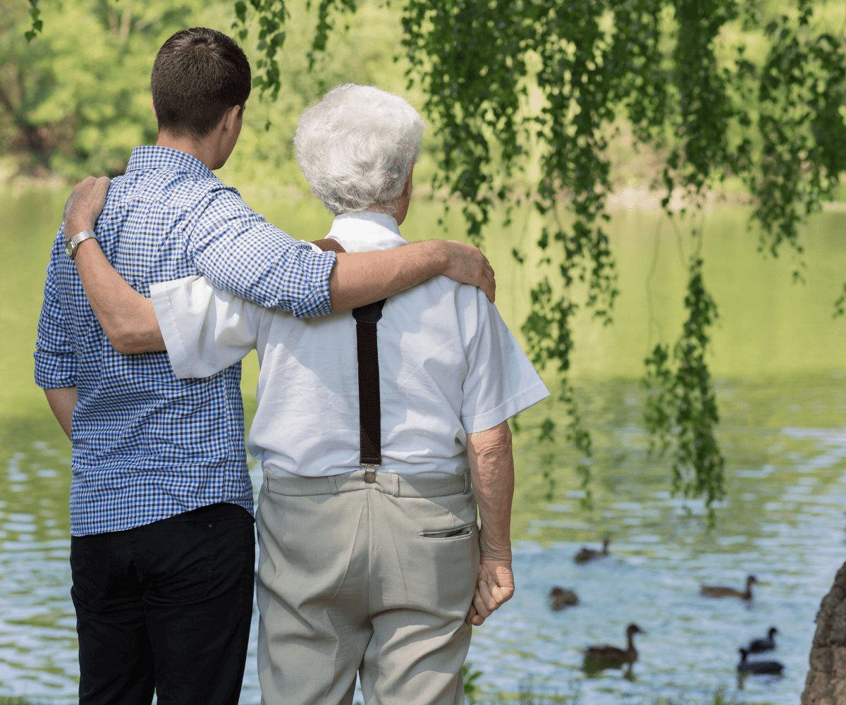 Elderly father and son facing a lake with their arms around each other.