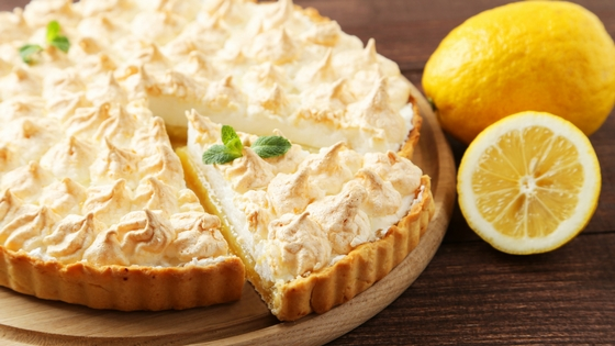 A lemon meringue pie garnished with peppermint, a slice cut out of it and a whole lemon and a sliced lemon on the table next to it.