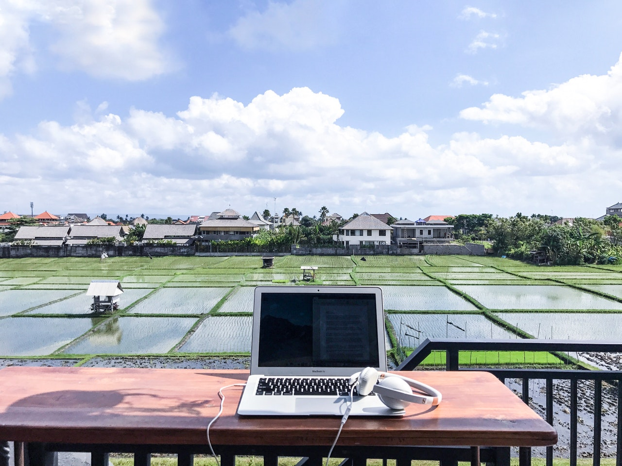 Laptop on a table looking over rice fields; digital nomad safety