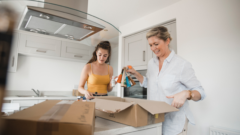 A mom and teenage daughter unpacking after a move