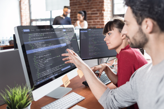 Web application development: Two co-workers look at lines of code