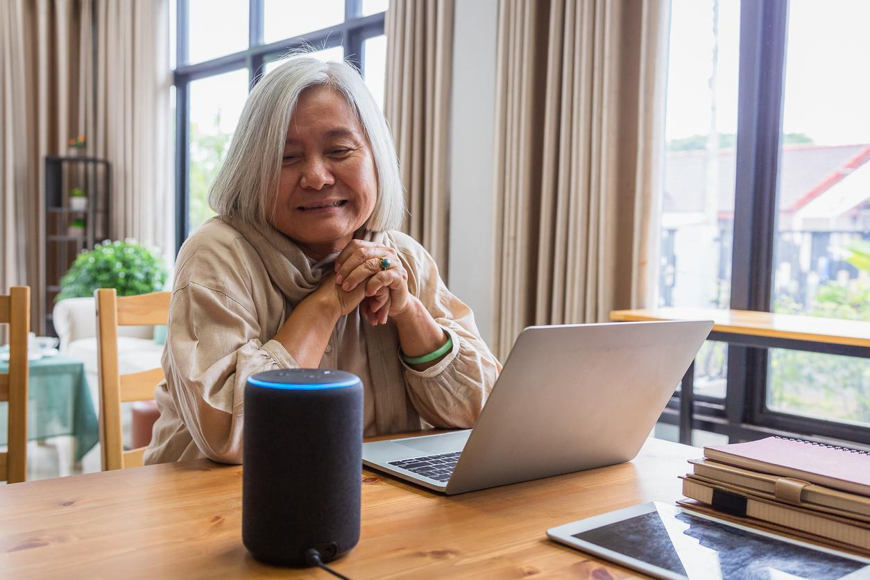 senior-woman-working-with-laptop-and-voice-assistant