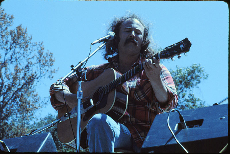 David Crosby singing and playing guitar outside.