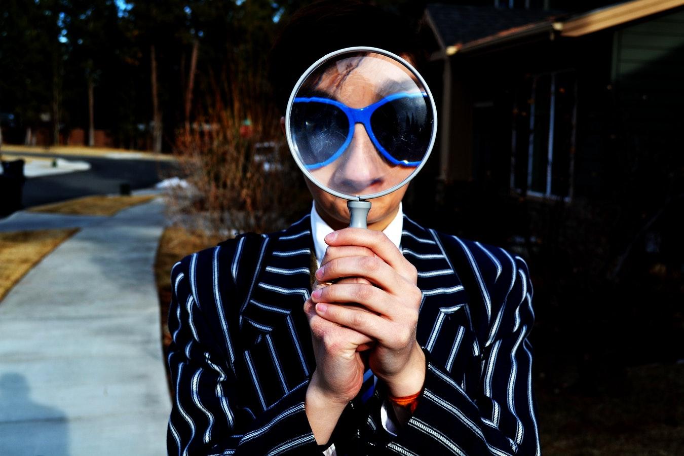 一個穿著條紋西裝的人拿著放大鏡。