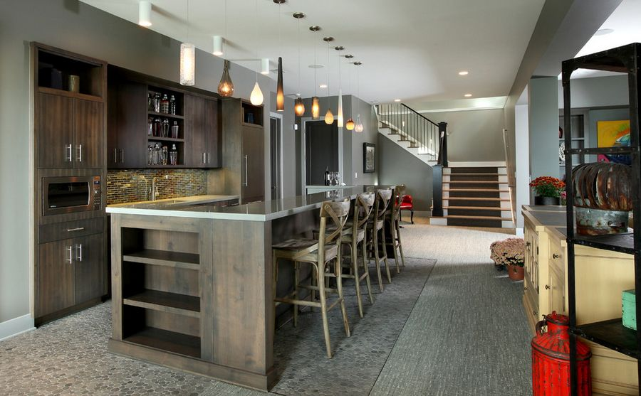 basement bar with stained wood cabinets, large wood island, glass light fixtures and neutral colors