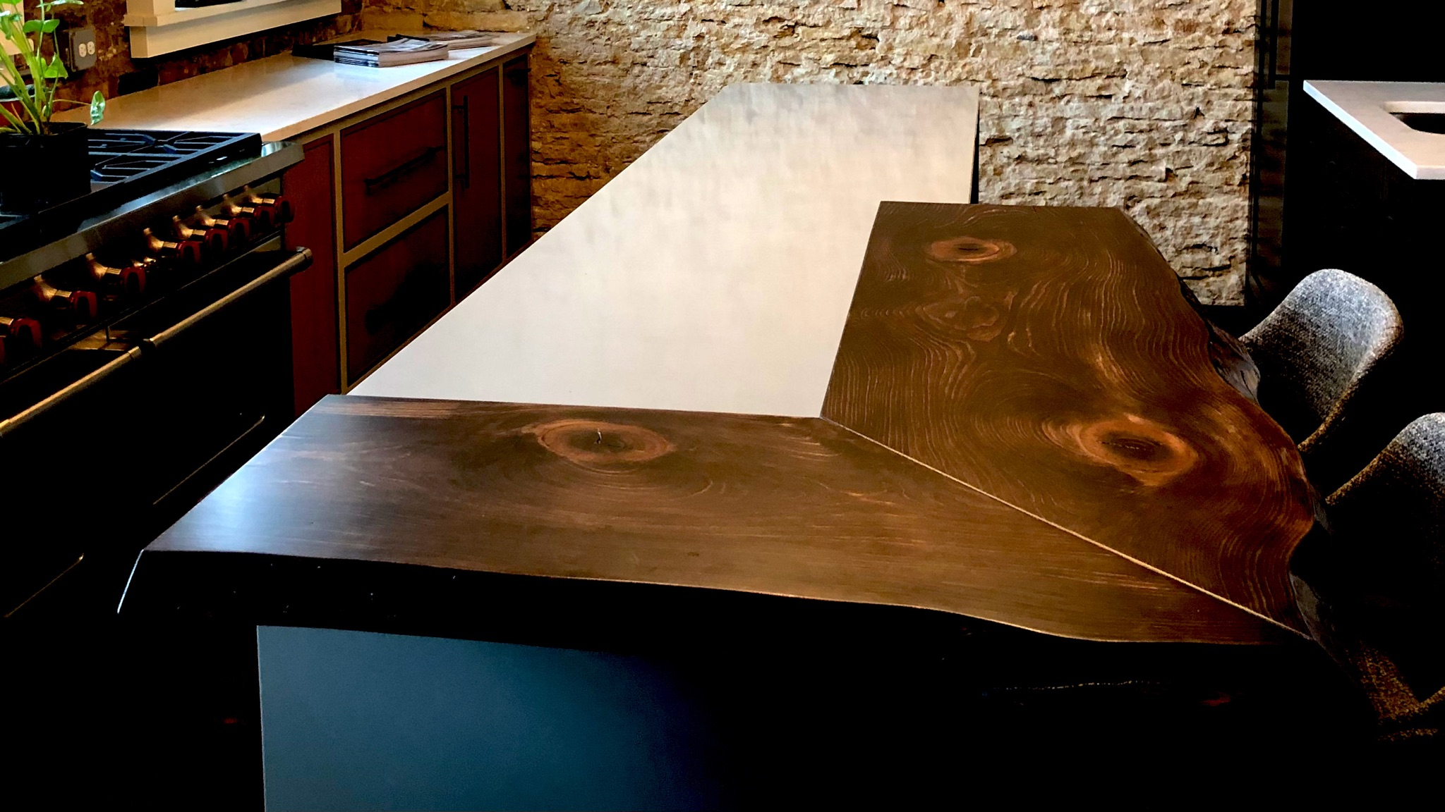 Kitchen mixed material island with quartz and a  live edge wood bar top.