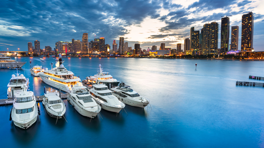 Skyline of Miami at night, with some docked yacht in front of it.