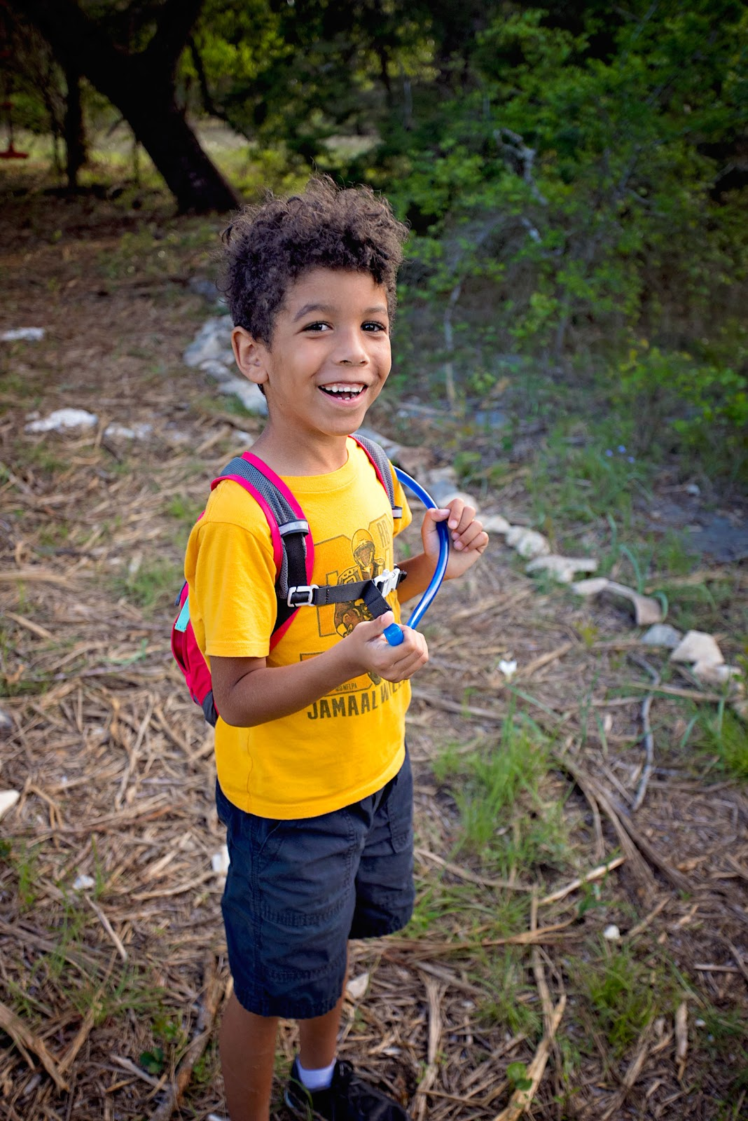 Little boy standing on a trail with his water straw. Primo water best water dispenser.