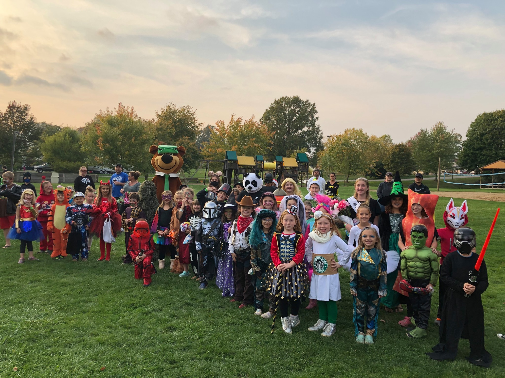 Kids in halloween costumes with Yogi Bear at campground.