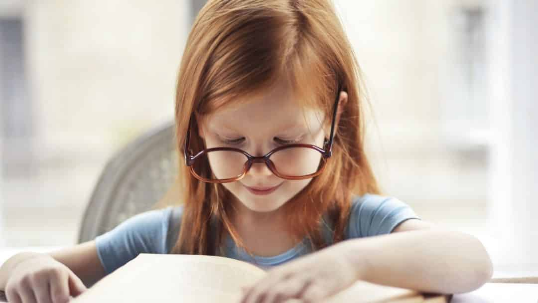 redheaded girl with tortoise shell glasses reading a book and smiling