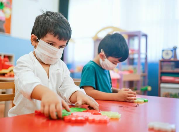 Masked children play with manipulatives.